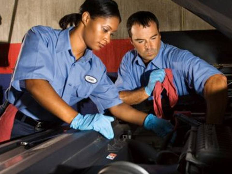 Mechanics looking at a car